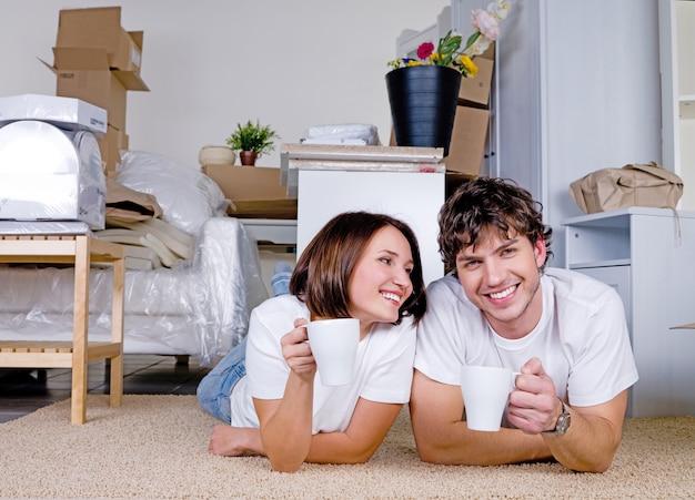 Mooi paar liggend op de vloer met kopjes thee na verwijdering in het nieuwe huis