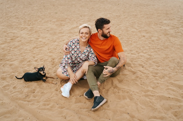 Mooi paar ontspannen op zand knuffelen en kussen tijdens het spelen met hun positieve hond