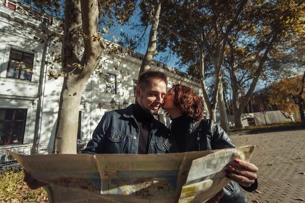 Mooi paar op vakantie met behulp van papieren stadskaart voor een routebeschrijving en zoenen