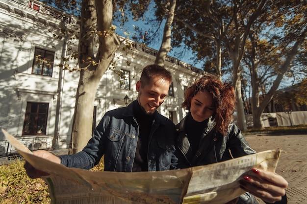 Mooi paar op vakantie met behulp van papieren stadskaart voor een routebeschrijving. reis vakantie, recreatie levensstijl.