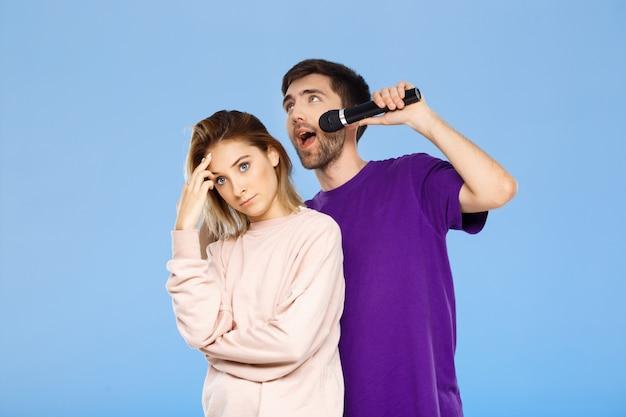 Mooi paar over blauwe muur. het zingen van de mens in microfoonmeisje beviel.