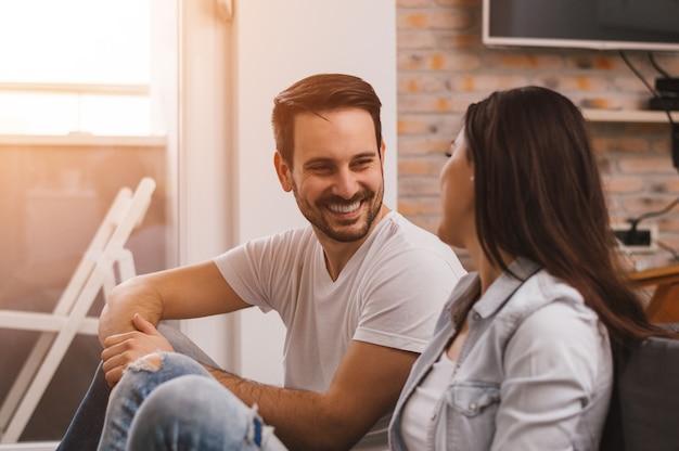 Mooi paar thuis praten, glimlachen, hebben een geweldige tijd samen