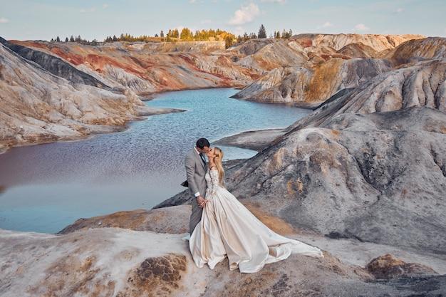 Mooi paar verliefd op een fantastisch landschap, bruiloft in de natuur, liefdeskus en knuffel