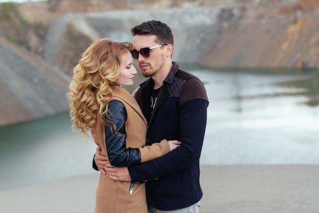 Mooi paar verliefd op valentijnsdag. gelukkig jong paar dat op de zandige bergen op een bewolkte dag loopt