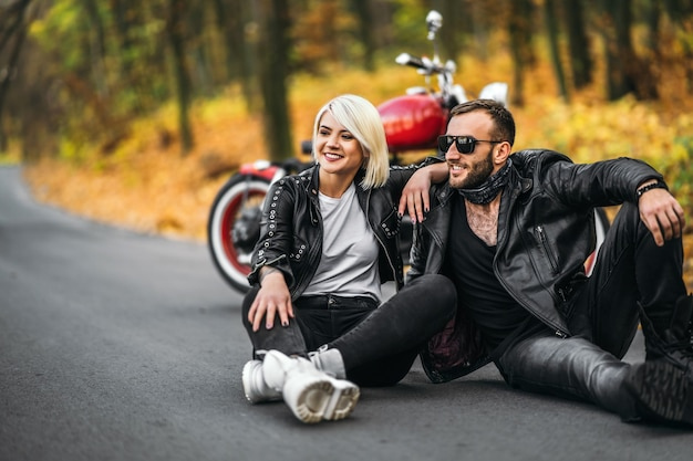 Mooi paar zittend in de buurt van rode motorfiets op de weg in het bos