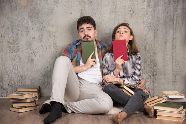 Mooi paar zittend op de vloer en boeken te houden