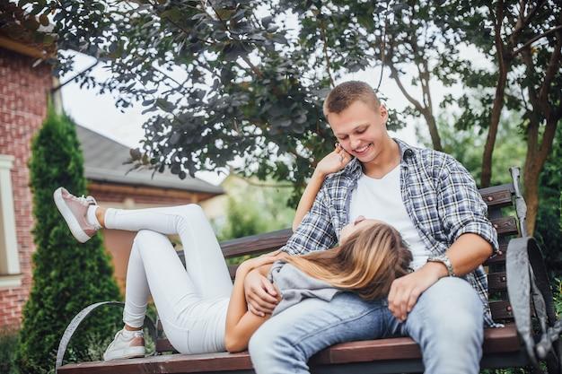 Mooi paar zittend op een bankje. glimlachende man en vrouw die elkaar bekijken. het meisje ging op de bank liggen en legde haar hoofd op de benen van de man.