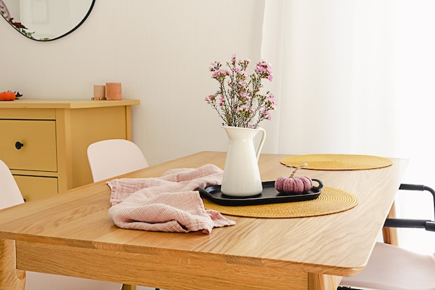 Mooi, paars bloemboeket in een witte kruik op het houten vat. in het interieur van een modern appartement in scandinavische stijl. het concept van thuiscomfort