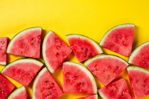 Mooi patroon met verse watermeloen plakjes op gele heldere achtergrond. bovenaanzicht. copy space.