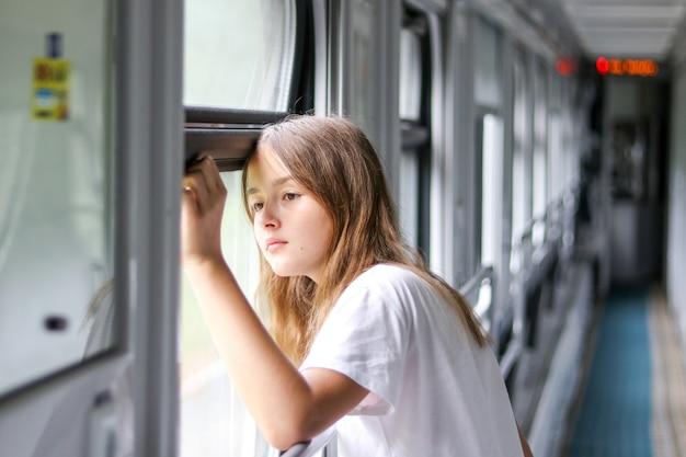 Mooi peinzend preteen meisje die droevig het venster in het compartimentvervoer bekijken binnen