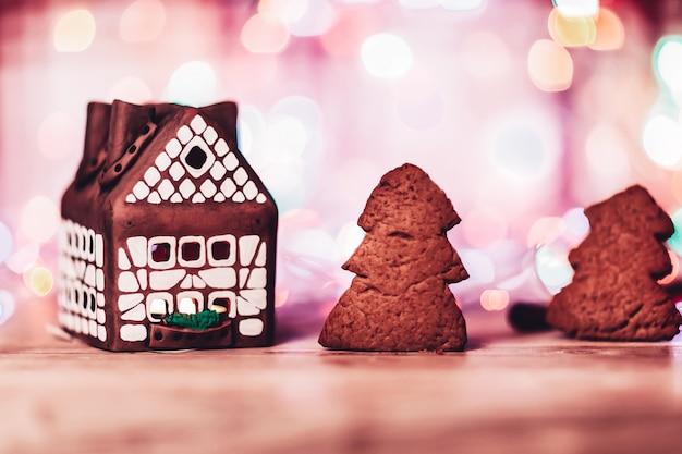 Mooi peperkoekhuis en peperkoek gegeten bij kerstmisachtergrond. de foto heeft een lege ruimte voor uw tekst