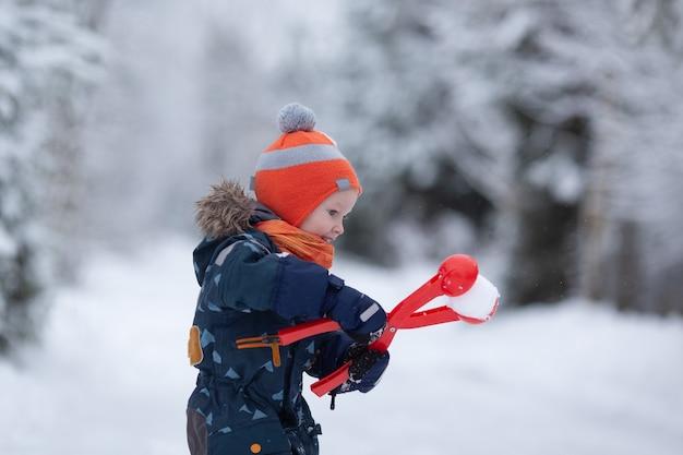 Mooi peuter meisje dragen winterkleren plezier buiten in besneeuwde dag. het meisje maakt sneeuwballen. kopieer ruimte
