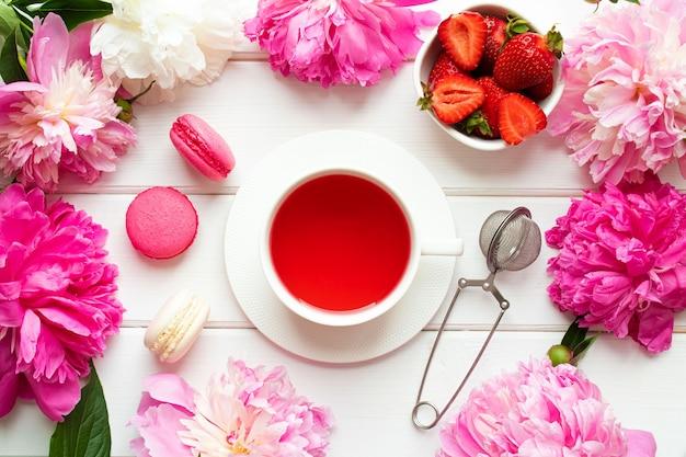 Mooi plat met aardbeien, macarons, fruitthee en pioenrozen op een witte houten tafel