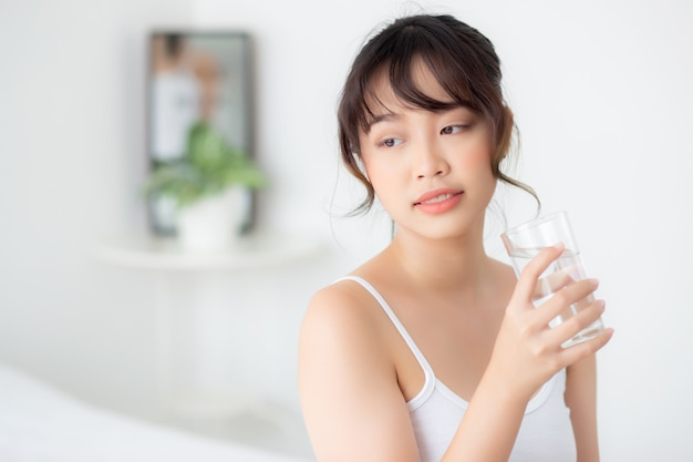 Mooi portret jonge aziatische vrouwenglimlach en drinkwaterglas met vers en zuiver voor dieet