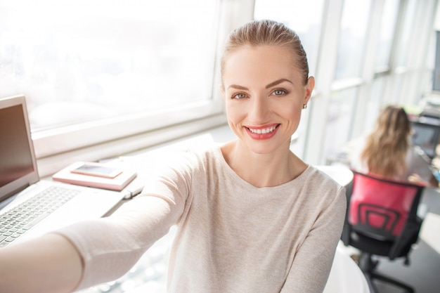Mooi portret van aantrekkelijke vrouw die aan de camera en het glimlachen kijkt