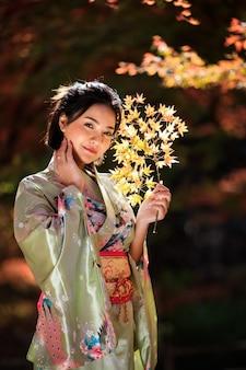 Mooi portret van aziatische vrouw die japanse gouden kimono in het park draagt