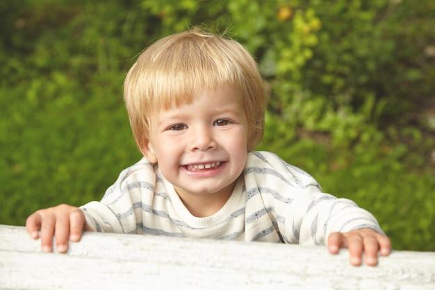 Mooi portret van blond glimlachend kind. klein kind buiten spelen in de zomertuin dichtbij huis. bruine ogen, melktanden, kleine vingers zijn ongelooflijk mooi. jeugd concept.