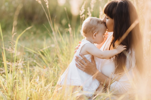 Mooi portret van charmante moeder en mooie kleine dochter lopen over het veld