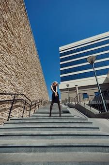Mooi portret van een blonde vrouw tegen een bakstenen muur op straat in een zwarte strakke jurk