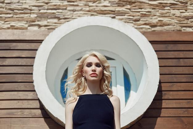 Mooi portret van een blonde vrouw tegen een bakstenen muur op straat in een zwarte strakke jurk.