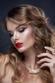 Mooi portret van een jong meisje, professionele make-up met rode lippenstift. op de nek sieraden gemaakt van parels, geschoten tegen een donkere achtergrond. schone huid, schoonheid.