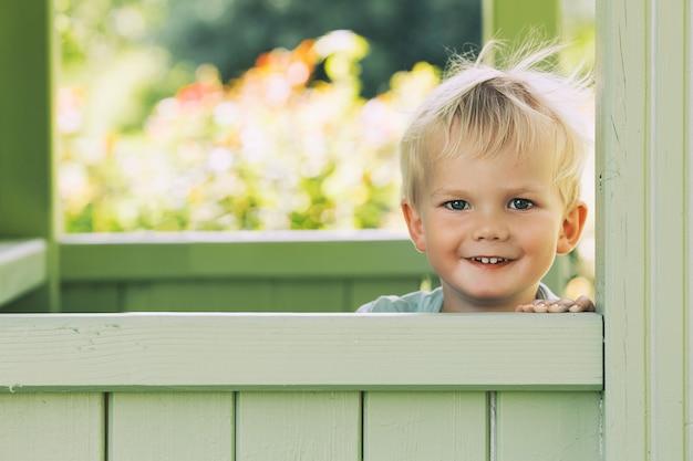 Mooi portret van een lachend jongetje buitenshuis afbeelding van kindertijd en gezin