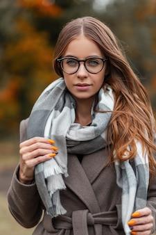 Mooi portret van een mooie jonge hipster vrouw met blauwe ogen in glazen in een vintage gebreide trui in een herfst jas buitenshuis. aantrekkelijke schattig modieus meisje mannequin wandelingen in het park.