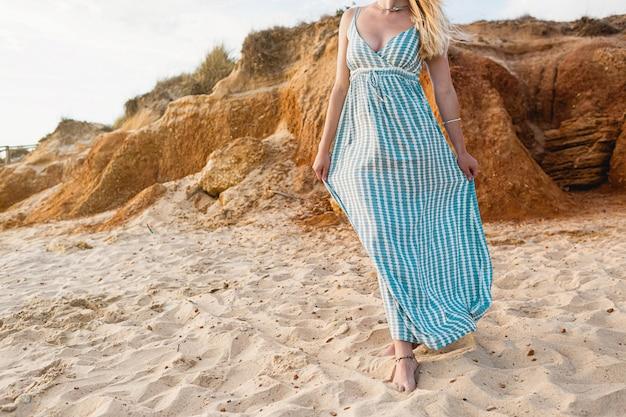 Mooi portret van een onherkenbare blanke vrouw, gekleed in een tie dye zomerjurk op het strand tijdens de zonsondergang