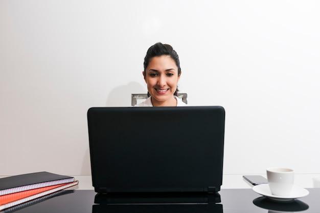 Mooi portret van een vrouw die in haar geïmproviseerde bureau thuis door beperkingsmaatregelen werkt. concept van thuiswerken.