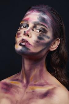 Mooi portret van een vrouw met het tekenen van verf op het gezicht en lichaam