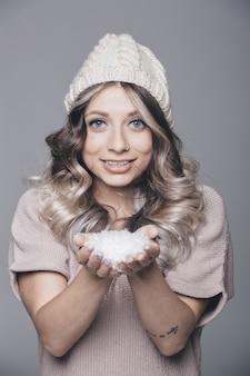 Mooi portret van jonge aantrekkelijke vrouw in gebreide kleding op besneeuwde achtergrond