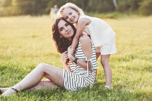 Mooi portret van meisje en haar dochter omhelzen elkaar buiten
