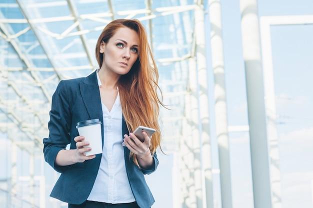 Mooi portret van succesvolle zakenvrouw in zakelijke kleding, kopje warme drank en telefoon te houden.