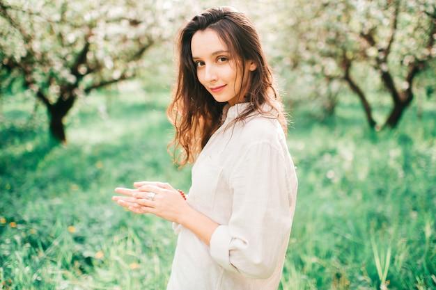 Mooi portret van vrij het donkerbruine jonge meisje stellen in smaragdgroene bloeiende spting tuin