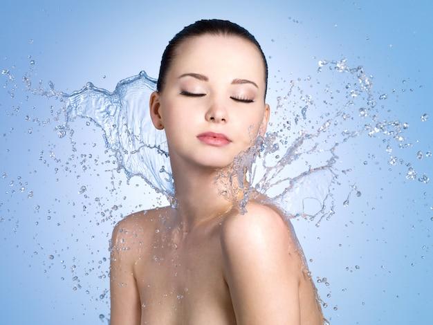 Mooi portret van vrouw met frisse huid in spatten van water - blauwe ruimte