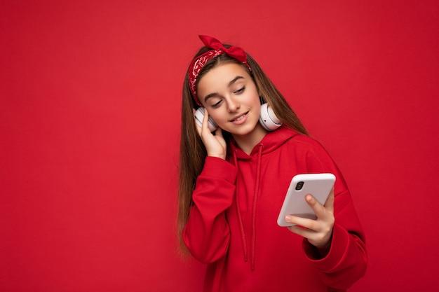 Mooi positief donkerbruin meisje die rode hoodie dragen die op rode achtergrond wordt geïsoleerd