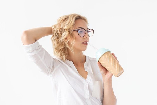 Mooi positief jong meisje in een wit overhemd houdt een cocktail in haar handen poseren voor een witte achtergrond. concept van desserts en cocktails.