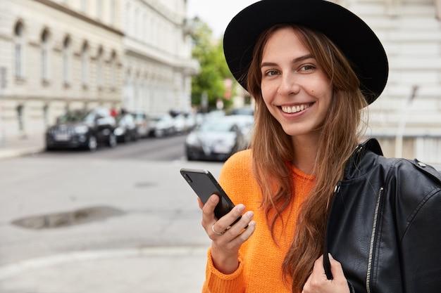 Mooi positief vrouwelijk model draagt zwarte hoed, oranje trui, heeft leren jas op schouder