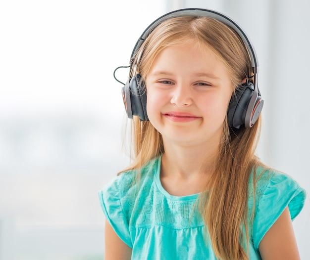 Mooi preteen meisje luistert naar haar favoriete band in een gloednieuwe koptelefoon