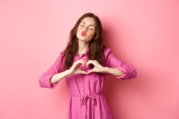 Mooi romantisch meisje glimlachen, hartgebaar tonen, staande in mooie jurk tegen roze muur. kopieer ruimte