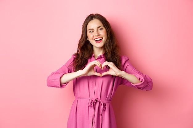 Mooi romantisch meisje glimlachen, hartgebaar tonen, staande in mooie jurk tegen roze muur.