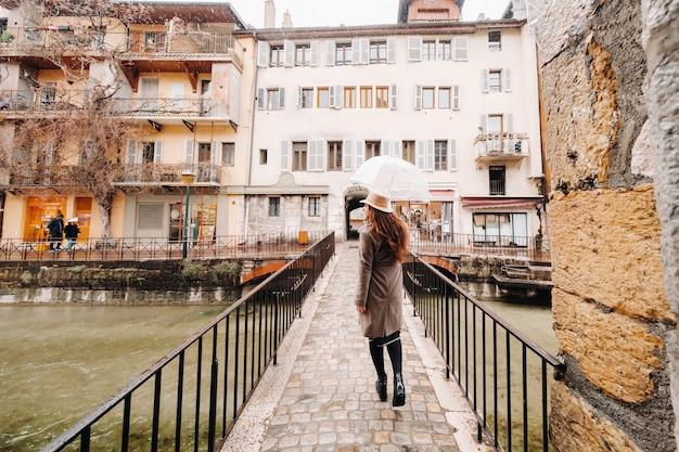 Mooi romantisch meisje in een jas en hoed met een transparante paraplu in annecy