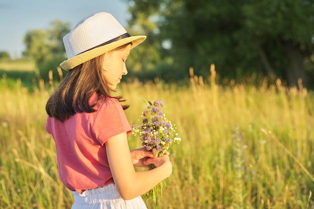 Mooi romantisch meisje in hoed, jurk verzamelen boeket van wilde bloemen in zonnige weide, pittoresk landschap, gouden uur, kopieer ruimte. jeugd, zomer, natuur, schoonheid, kinderconcept.