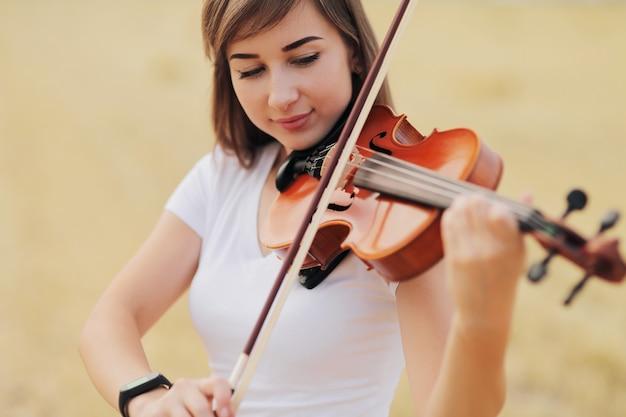 Mooi romantisch meisje met losse haren viool spelen in het veld.