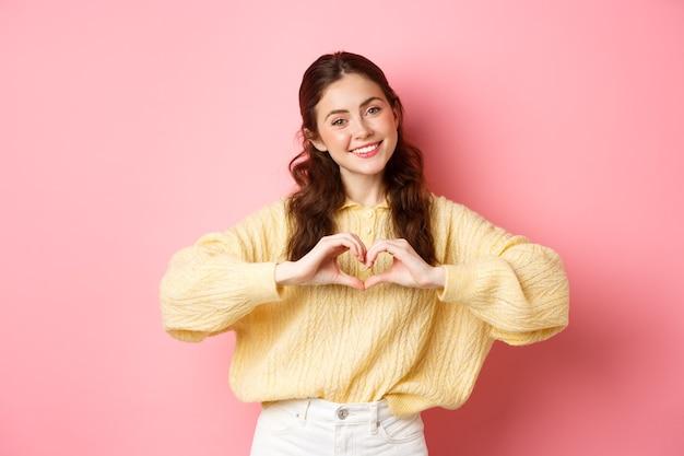 Mooi romantisch meisje zegt 'ik hou van je', met een hartteken en lachend naar de camera, schattig staand tegen een roze muur.