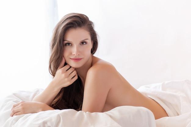 Mooi romantisch vrouw / meisjesbrunette die op het bed in haar ruimte thuis liggen