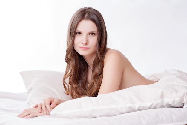 Mooi romantisch vrouwenbrunette die op het bed in haar ruimte thuis liggen.