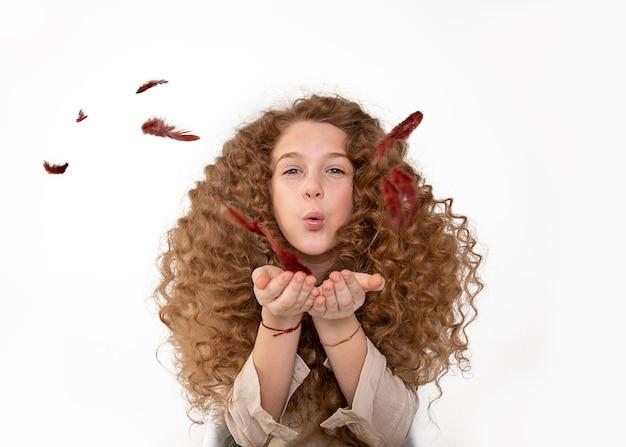 Mooi rood haar krullend lang roodharig meisje waait veren uit handen