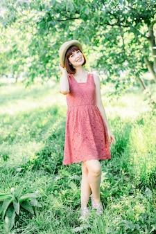 Mooi rood haar meisje staat op de achtergrond van de appeltuin ze houdt haar hoed tegen haar hoed en lacht een lieve glimlach. het meisje is gekleed in een blauwe jurk met een witte stip en een strohoed-panama.