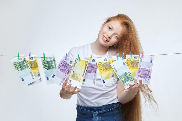 Mooi roodharig meisje hangt eurobankbiljetten aan een touw